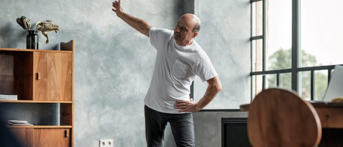 senior-man-practicing-yoga-trikonasana-pose-at-the-62WD8QG