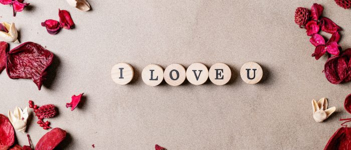 Word love made with wooden circle stamps with flowers over brown texture background. Top view, flat lay. Copy space